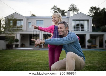Smiling father and daughter pointing in the garden