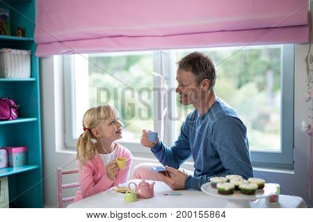 Father and daughter playing a tea set role play in her room