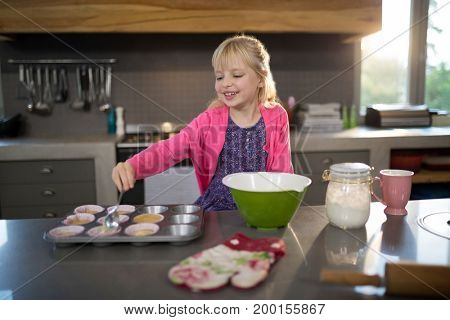 Smiling girl pouring cupcake batter into the tray