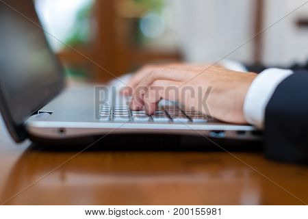 Male hands typing on a laptop keyboard