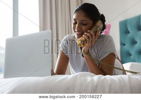 Young woman using laptop while talking on phone on bed at home