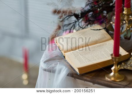 A table set with book and candles white background