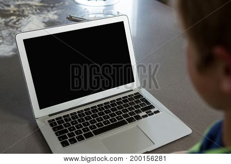 Cropped image of boy looking into laptop at kitchen counter