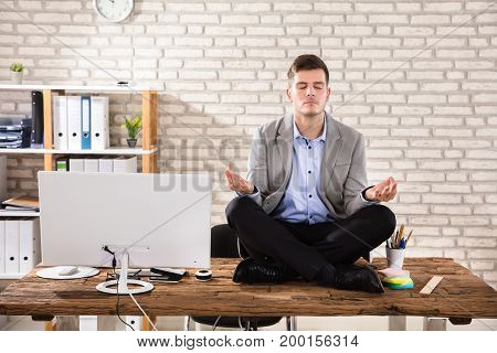 Young Businessman Sitting On Wooden Desk Meditating In Office