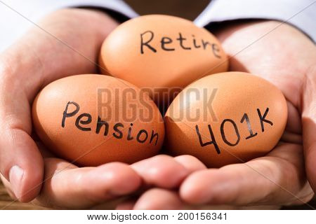 Close-up Of A Human Hand With Brown Egg Showing Pension And Retirement Text