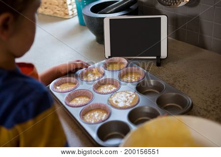 Boy holding muffin tin with cupcake holders by digital tablet at kitchen counter
