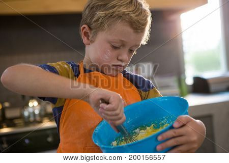 Boy mixing batter in blue container at kitchen