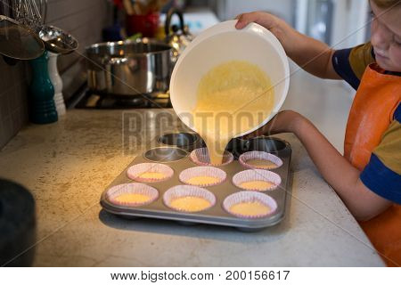Boy pouring batter in cupcake holders at kitchen counter