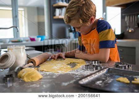 Boy making shapes from pastry cutter at kitchen counter