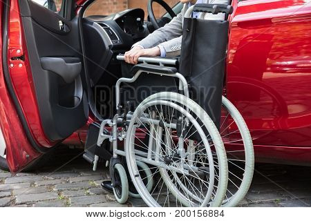Young Man Sitting In A Red Car Folding His Wheelchair On Street