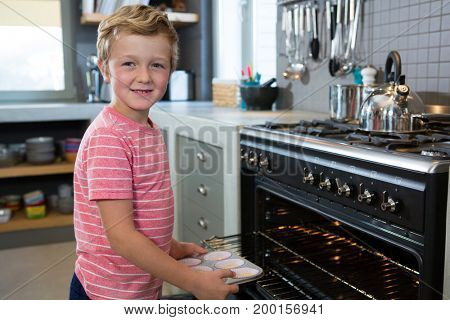 Portrait of boy holding muffin tin by oven in kitchen at home
