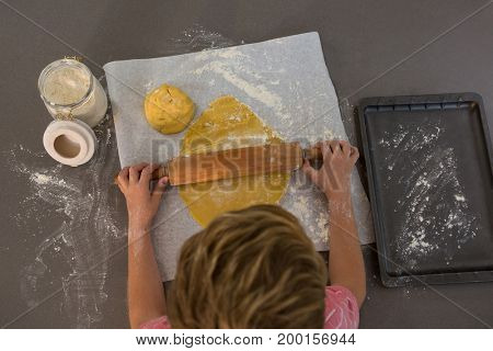 High angle view of boy rolling dough at kitchen counter