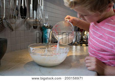 Boy pouring milk in batter at kitchen utensil