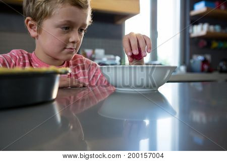 Innocent boy having food in kitchen at home