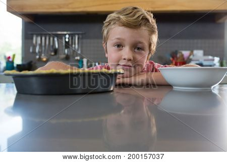 Portrait of boy by bowl at counter in kitchen