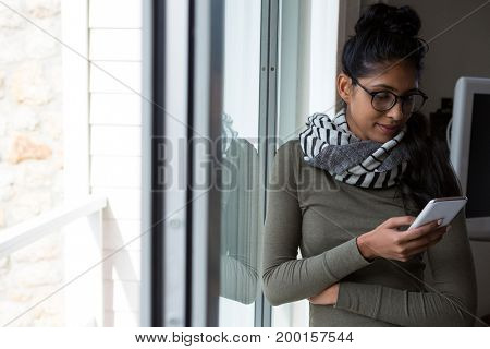 Young woman using phone by glass window at home