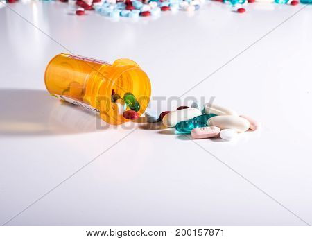Pill bottle spilling a variety of medications with pills scattered in the background