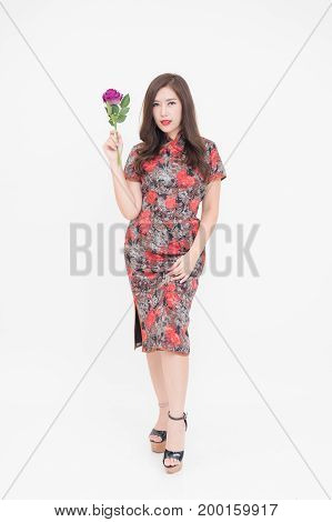 Beautiful young fashionable Asian woman holding flowers against a plain background