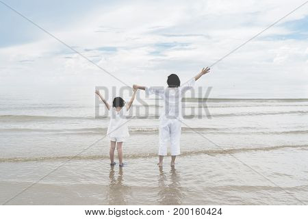 Happy Asian family mother and daughter standing on beach and raise up hand for freedom near sea. Happy family summer vacation concept.