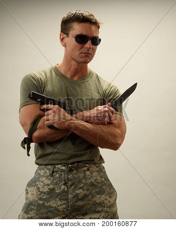 the handsome army guy is holding a pistol