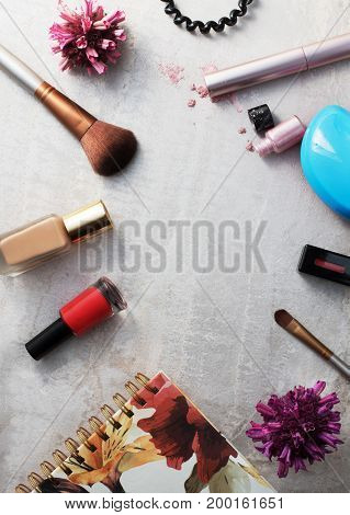 Beauty products everyday makeup vibrant background. Cosmetic essentials - mascara eyeshadow lipstick foundation and nail polish on a gray marble background top view