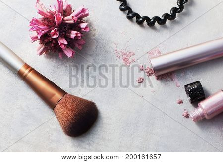 Beauty products everyday makeup vibrant background. Cosmetic essentials - mascara eyeshadow brush and hair elastic on a gray marble background top view