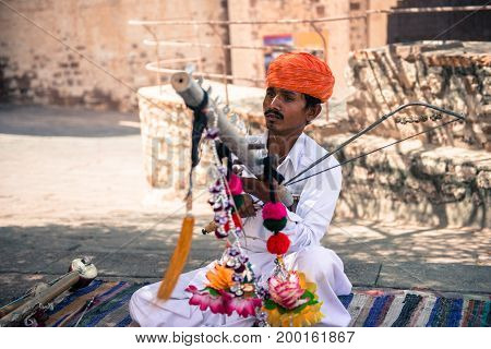 JODHPUR RAJASTHAN INDIA - MARCH 05 2016: Horizontal picture of local indian with mustache playing music inside Mehrangarh Fort in Jodhpur the blue city of Rajasthan in India.