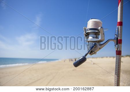 Fishing reel on rod detail with angling fishers at bottom on the sea Huelva Spain