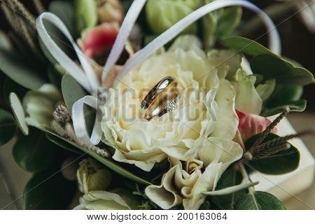 wedding rings on white flowers broun background