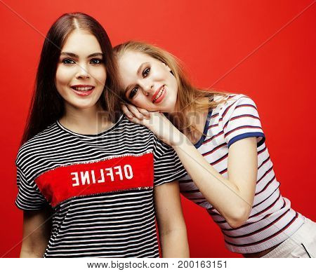 two best friends teenage girls together having fun, posing emotional on red background, besties happy smiling, lifestyle people concept close up
