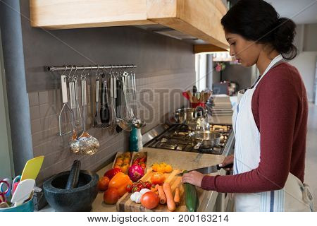 Side view of young woman cutting zucchini in kitchen at home
