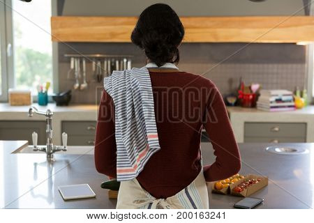 Rear view of woman cooking food in kitchen at home