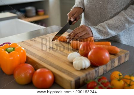 Mid section of woman cutting carrot at kitchen counter