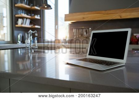 Laptop on kitchen counter at home