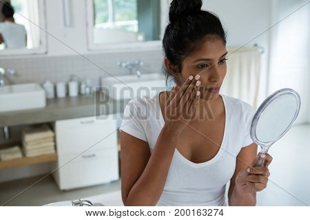 Woman holding hand mirror in bathroom at home
