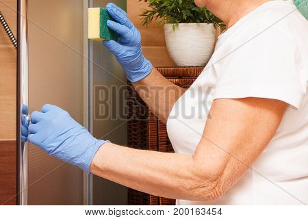 Hand Of Elderly Senior Woman Using Sponge And Cleaning Shower Cabin, Household Duties Concept