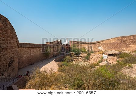 JODHPUR RAJASTHAN INDIA -MARCH 05 2016: Wide angle picture of the brick wall of Mehrangarh Fort with local vegetation in Jodhpur the blue city of Rajasthan in India.