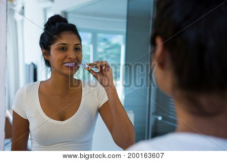 Woman brushing teeth with reflection on mirror in bathroom at home