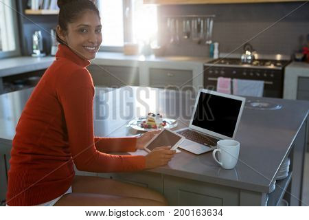 Portrait of smiling woman using digital tablet in kitchen at home