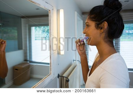 Young woman brushing teeth in bathroom at home