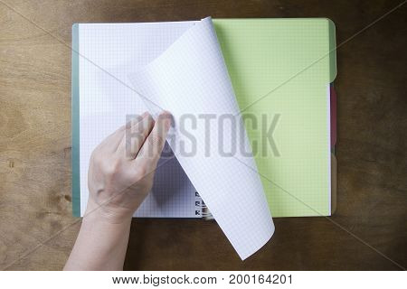 Hands flipping page notebooks on a wooden table