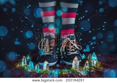 Girl in sneakers and striped socks inside an enchanted which circle made with crystals on a dark background with bokeh. Fairytale scene representing a Leprechaun