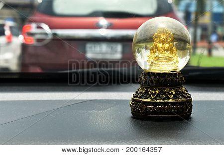 little buddha statue behind windshield in car ,text in thai language is Phraphutthachinnarach