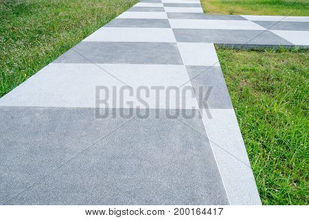 Chess concrete pathway grey and white pattern and green grass