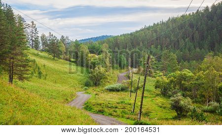 Landscape of the Altai Mountains in a summer clear day. Automobile winding road leaving in the distance in the mountains between the green coniferous forest and power lines blue sky with clouds