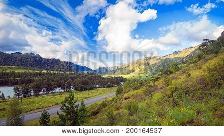 Landscape of the Altai mountains on a summer day. An automobile road that goes to the distance into the mountains between the green coniferous forest the blue sky with clouds in the mountains