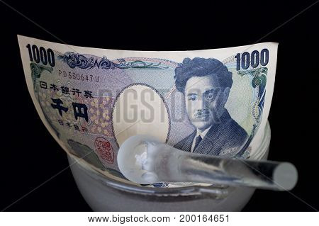 Japanese one thousand yen note in a glass mortar with a pestle.