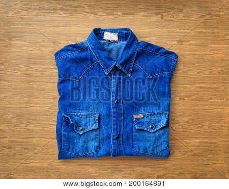 Close up blue denim shirts jean on brown wooden table top