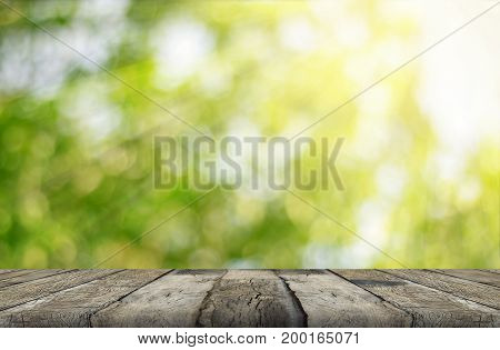 wood table and green leaf bokeh blurred for nature background