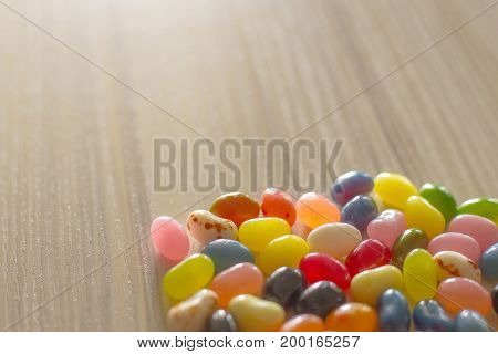 A Pile of jelly beans multi color on wood table